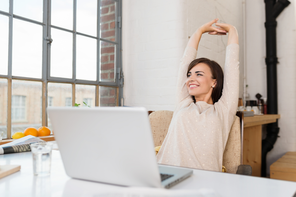 Happy relaxed young woman engaging in remote work in her kitchen with a laptop in front of her stretching her arms above her head and looking out of the window with a smile