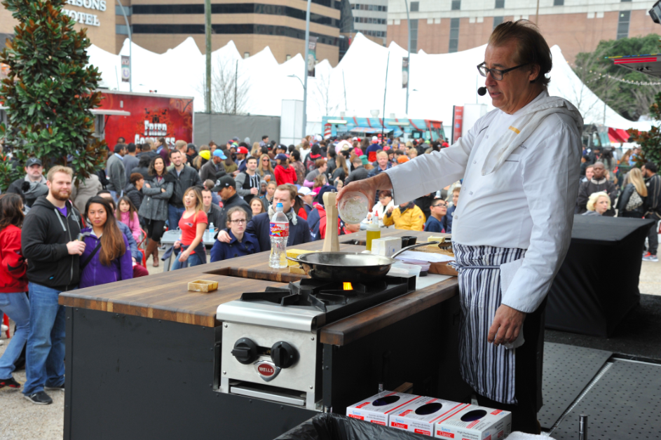 chef cooking in front of large group